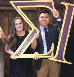 Thong Ta and other Phi Sigma Pi members holding Greek letters